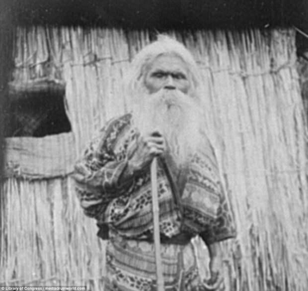 Пожилой айн с палкой у хижины айны, история, народ, фотография