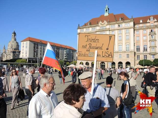 "Русский флаг и плакат ""Дружба с Россией"" на митинге в Дрездене. Фото: Дарья АСЛАМОВА"