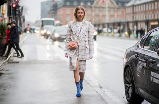 девушка в клетчатом костюме идет по улице