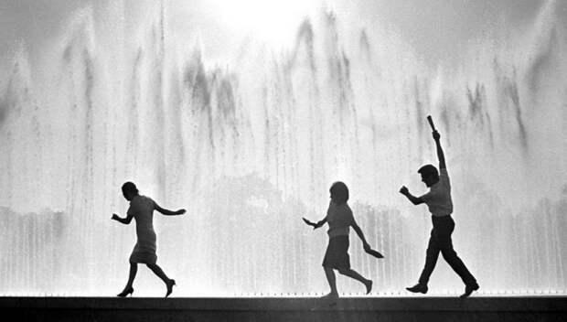 Молодые люди получают удовольствие бегая босиком по бордюру фонтана, ловя брызги воды.