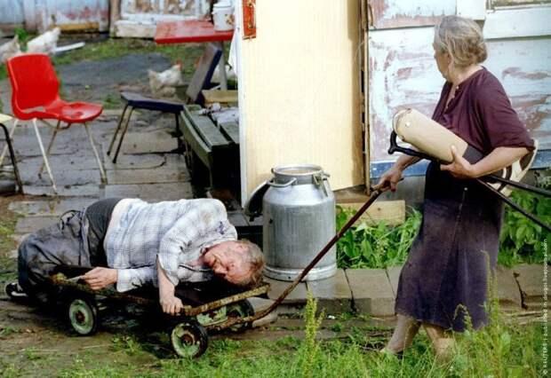 Жена везет на тележке пьяного мужа-инвалида.