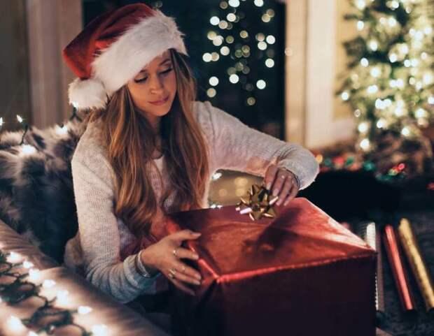 девушка в шапке санты с подарком в руках