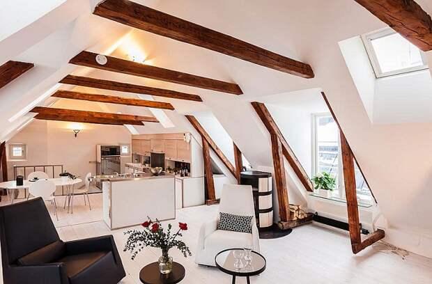 Удачное размещение кухни переходящей в гостиную под чердаком, что добавляет определенного шарма декору.