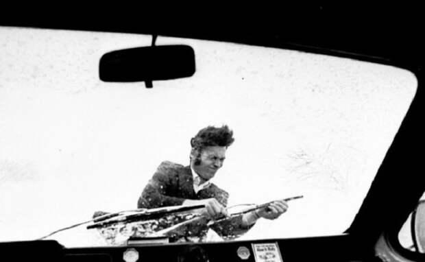 Шофер в дождь пытается поставить дворники на лобовое стекло своей машины.