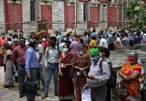 FILE PHOTO: People wearing protective face masks wait to receive their second dose of COVISHIELD, a coronavirus disease (COVID-19) vaccine manufactured by Serum Institute of India, outside a vaccination centre in Kolkata, India, May 12, 2021. REUTERS/Rupak De Chowdhuri/File Photo