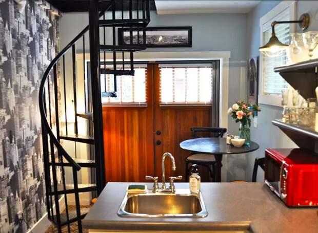 Винтовая кованая лестница черного цвета соединяет первый и второй этажи (Bird House, штат Северная Каролина). | Фото: tinyhousetalk.com.