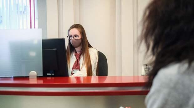Сотрудница банка в защитной маске ведет прием посетителей в одном из отделений Московского кредитного банка - РИА Новости, 1920, 04.10.2020