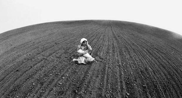 Женщина с ребенком на руках посередине вспаханного поля. 1987 год.