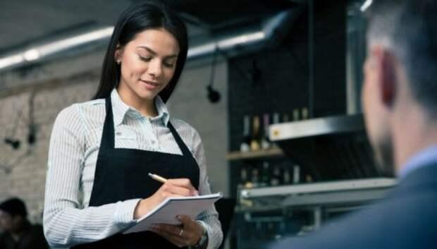 девушка-официант принимает у мужчины заказ