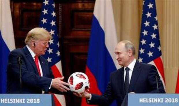 U.S. President Donald Trump receives a football from Russian President Vladimir Putin as they hold a joint news conference after their meeting in Helsinki, Finland July 16, 2018. REUTERS/Grigory Dukor
