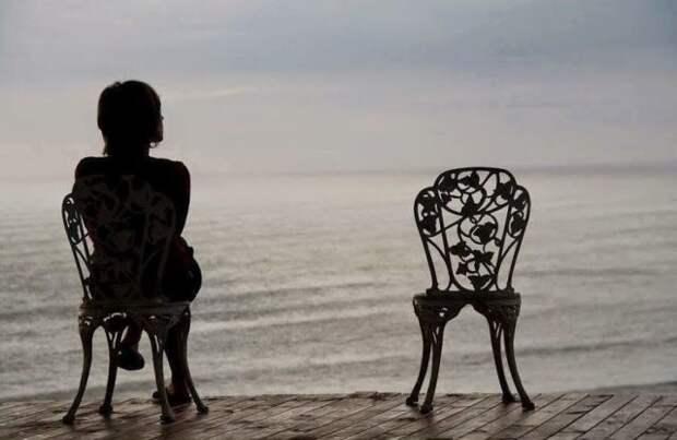 девушка сидит на стуле на берегу моря