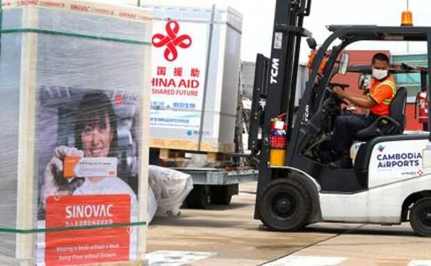 На фото: рабочий перевозит упаковку китайской вакцины против COVID-19 в международный аэропорт Пномпеня в Пномпене, Камбоджа, после того, как страна получила новую партию китайских вакцин.