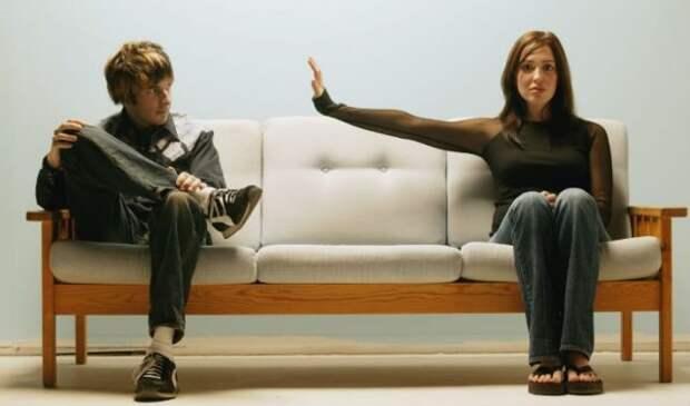 парень и девушка сидят на разных концах дивана