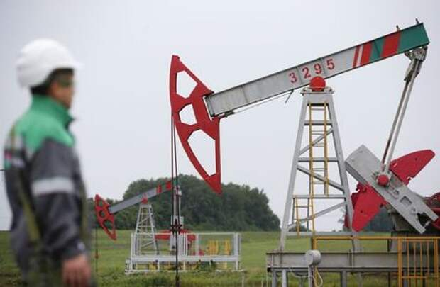 A worker looks at a pump jack at an oil field Buzovyazovskoye owned by Bashneft company north from Ufa, Bashkortostan, Russia, July 11, 2015. REUTERS/Sergei Karpukhin/File Photo