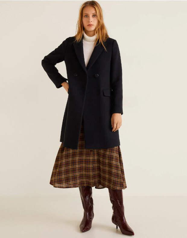 Модель в черном пальто в мужском стиле