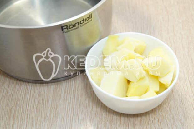Воду в кастрюле вскипятить, картофель очистить и нарезать кубиками. Сварить картофель до полуготовности.