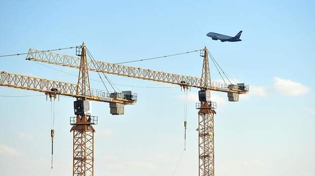 Самолет над башенными кранами