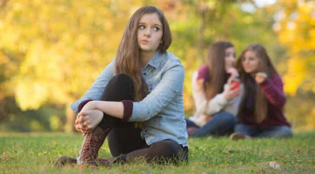 девушка сидит в стороне от подруг