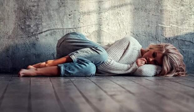 девушка лежит на полу у стены