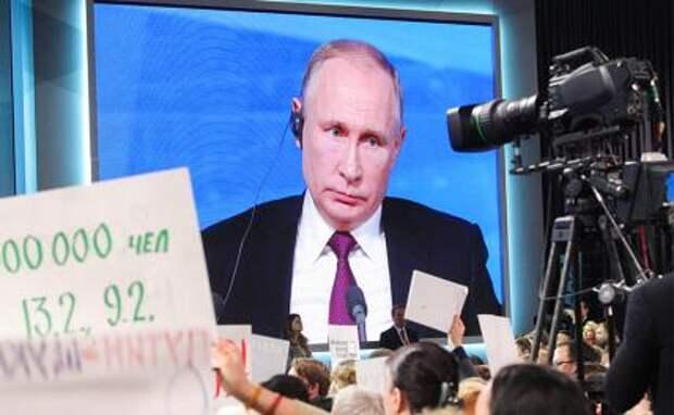 На фото: президент РФ Владимир Путин (на экране) во время большой ежегодной пресс-конференции