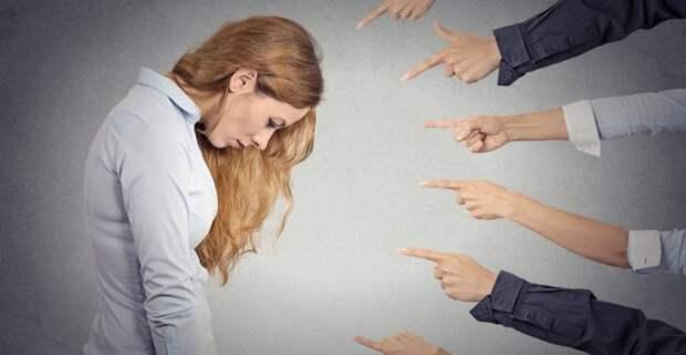 люди показывают пальцем на девушку, опустившую голову
