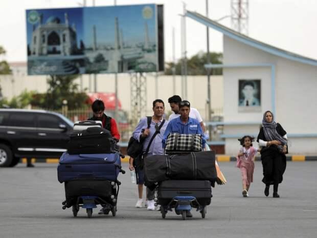 На фото: пассажиры идут к терминалу вылета международного аэропорта имени Хамида Карзая в Кабуле, Афганистан, 14 августа 2021 года.