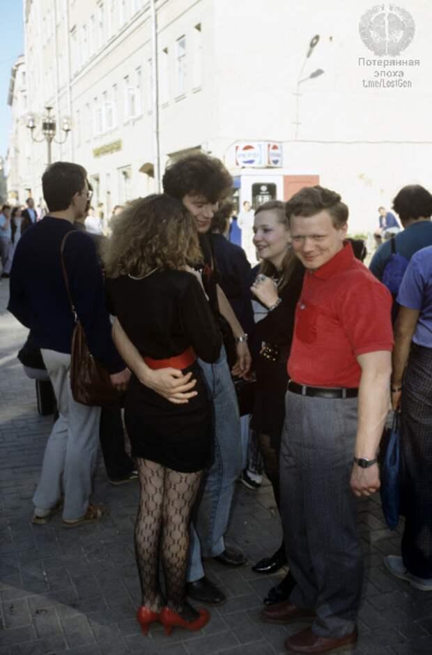 Молодые люди весело гуляют, вдали можно увидеть ларек с пепси-колой