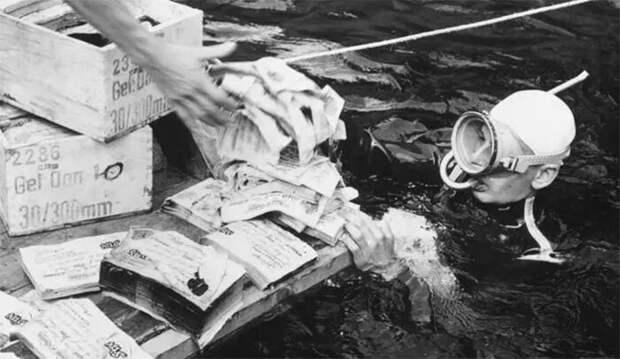 Аквалангист передает фальшивые нацистские банкноты, найденные в озере Топлиц Фото Keystone / Getty Images