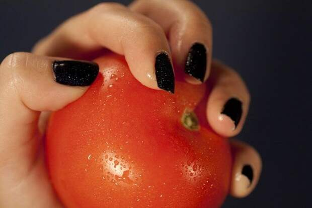 View of a woman hands holding a red tomatoe.