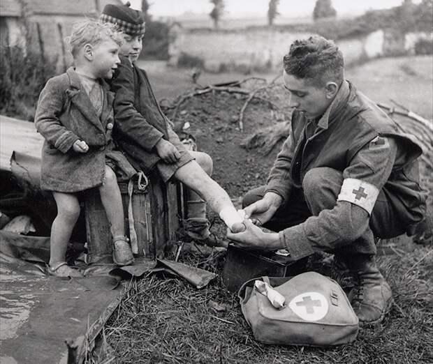 Канадский врач накладывает бандаж на ногу раненого ребенка, 1944 год.