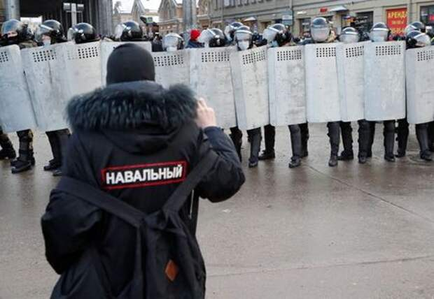 """A demonstrator stands in front of law enforcement officers during a rally in support of jailed Russian opposition leader Alexei Navalny in Saint Petersburg, Russia January 31, 2021. The writing on the jacket reads: """"Navalny"""". REUTERS/Anton Vaganov"""