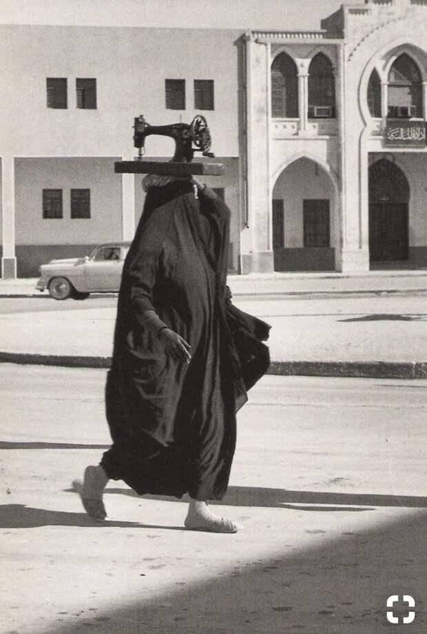 Ничего особенного. Просто женщина переносит швейную машинку. Где-то на улице Кувейта. 1955 история, мгновения жизни, фотография