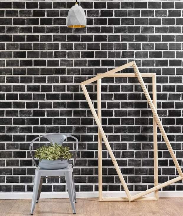 Деревянные рамки возле стены с обоями под черный кирпич