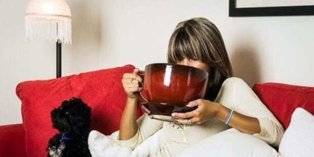 женщина с большой чашкой кофе на диване