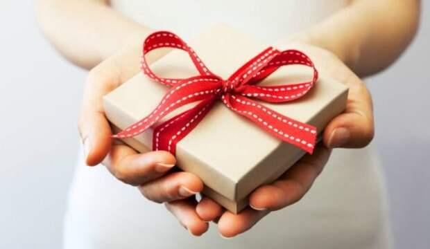 коробка с красной лентой в женских руках