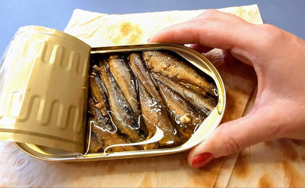 Наносим банку шпротов равномерно на лаваш и сворачиваем: закуску из ресторана подаем за 15 минут