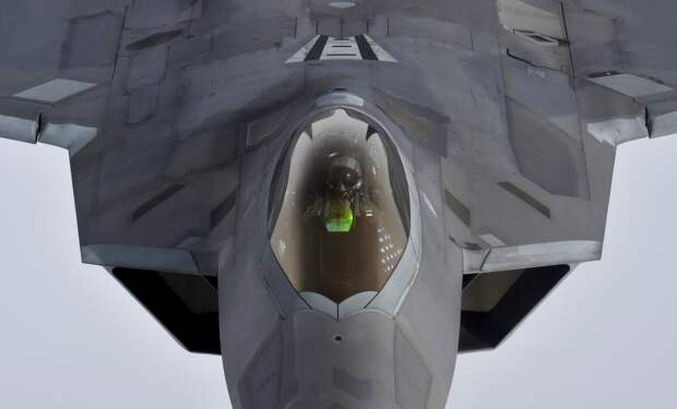 A pilot looks up from a U.S. F-22 Raptor fighter as it prepares to refuel in mid-air with a KC-135 refuelling plane over European airspace during a flight to Britain from Mihail Kogalniceanu air base in Romania