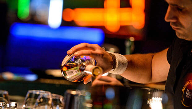 Бармен разливает напитки за барной стойкой в клубе