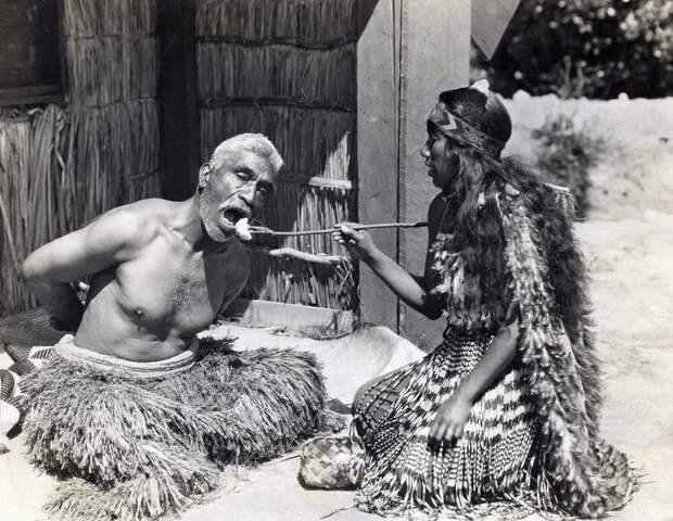 Врач и по совместительству шаман Маори кормит жителя Новой Зеландии, 1930 история, мгновения жизни, фотография