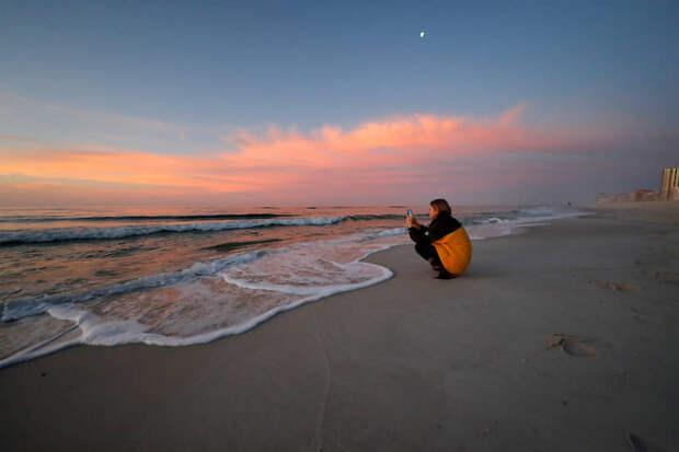 Орандж-Бич, штат Алабама, США. Девушка фотографирует закат на городском пляже