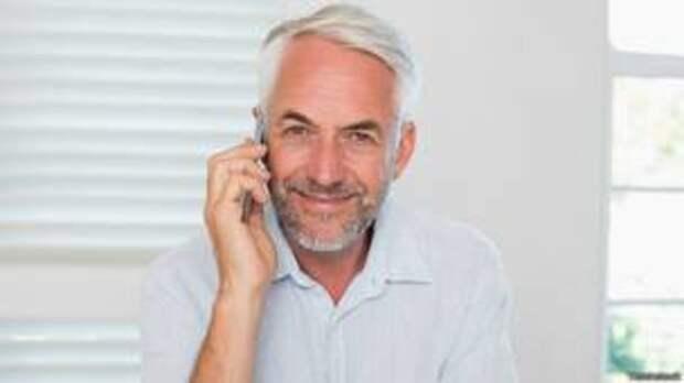 Седой мужчина разговаривает по телефону