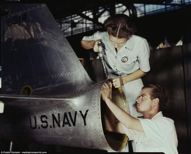 Virginia Davis, a riveter in the assembly and repair department of the Naval Air Base, supervises Charles Potter, a NYA trainee from Michigan