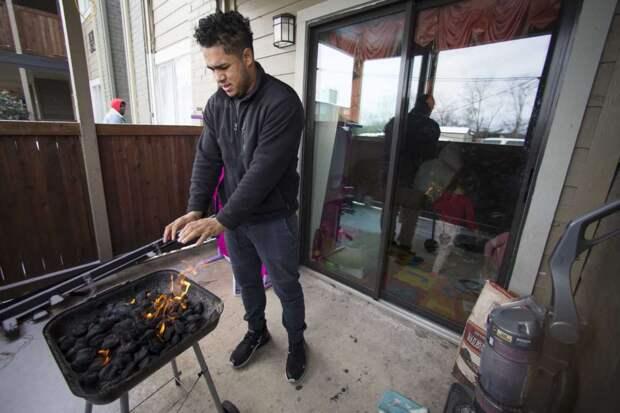 Кевин Моразан греет руки на  угольном гриле для приготовления пищи после отключения электроэнергии вследствие ночного снегопада и ледяного дождя в районе Гринспойнт в понедельник, 15 февраля 2021 года, в Хьюстоне. Отопление у него электрическое