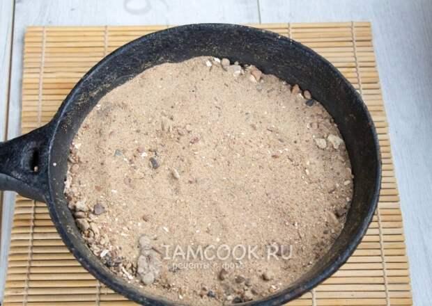 Насыпать на сковороду песок