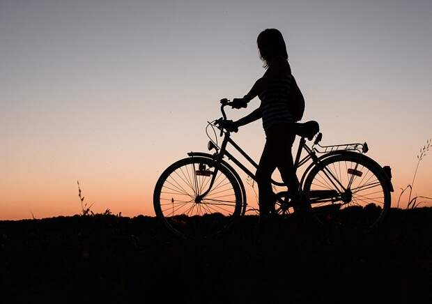 силуэт девушки с велосипедом на закате