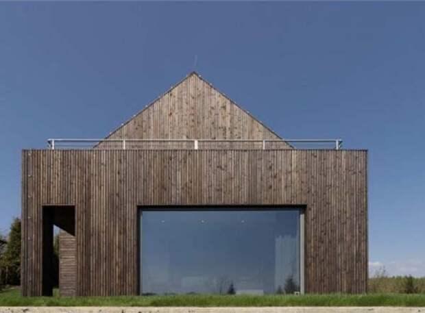 Деревянный дом, который многие называют бесформенным зданием, а кто-то видит в огромном окне и прямом фасаде некую изюминку.
