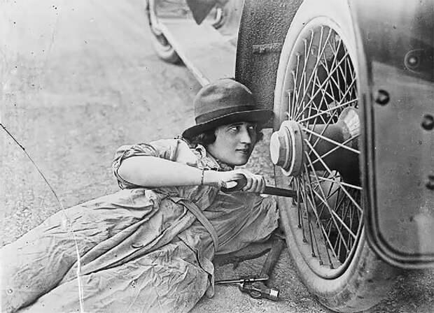 Женщина-водитель во время Первой мировой ремонтирует колесо 20 век, автомеханик, женщина 20 век, женщина и авто, женщина и машина, механики, ретро фото, старые фото