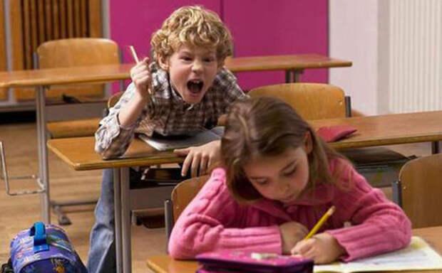 мальчик за задней партой кричит на девочку впереди