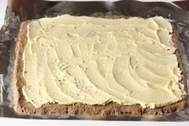 На печёночный паштет выкладываем желтковое масло и размазываем его по всей площади паштета, немного отступая от краёв. Это делать легко столовой ложкой, опущенной в горячую воду на несколько секунд и насухо вытертой.