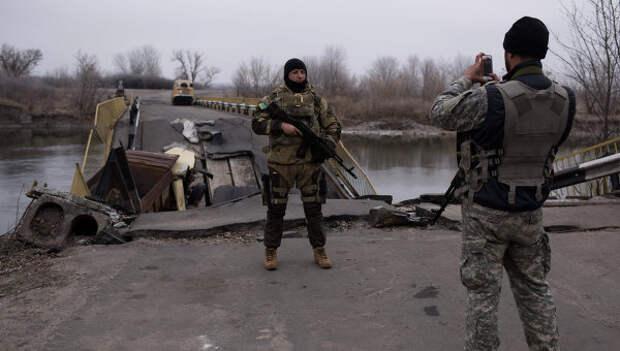 Украинские военные фотографируются на фоне разрушенного моста через реку Северский Донец